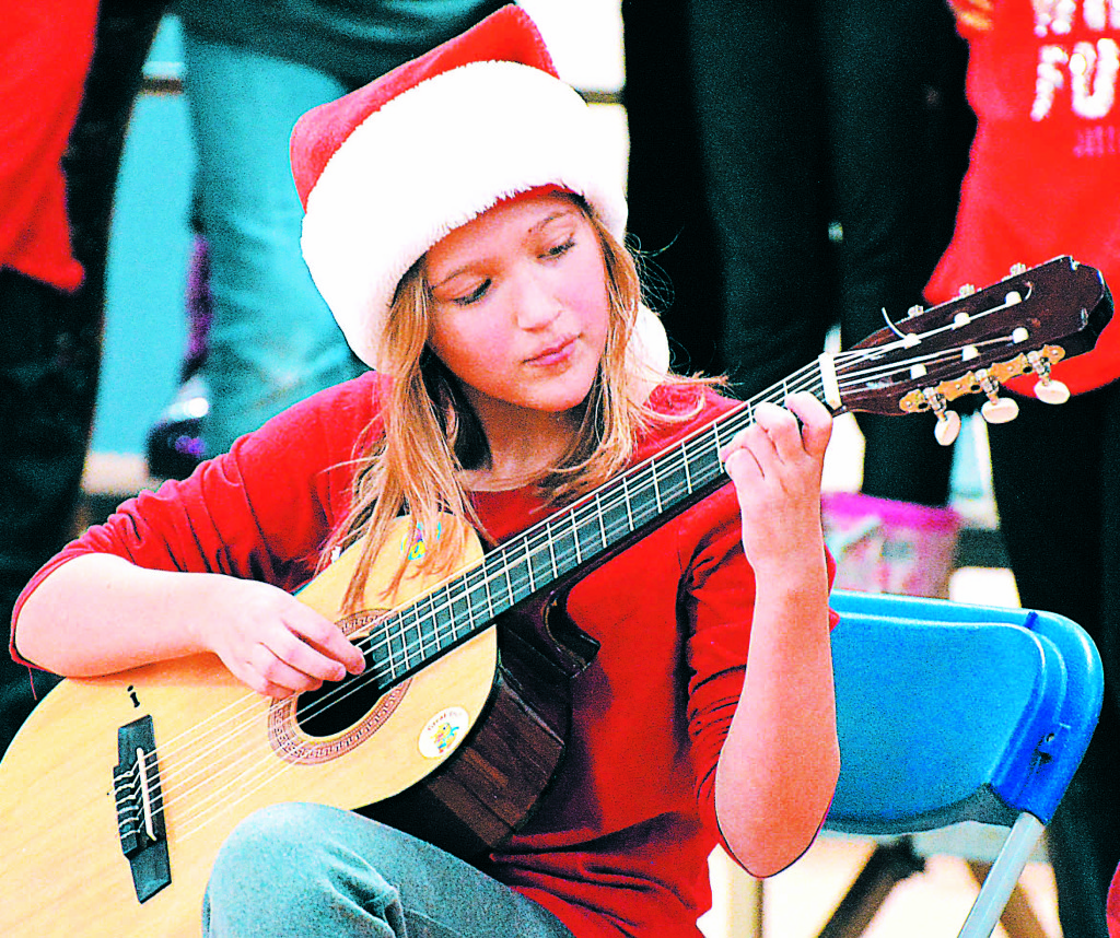 Clear Lake student Allison Hepp plays Christmas tunes on her guitar. Photos by C.J. Carnacchio.