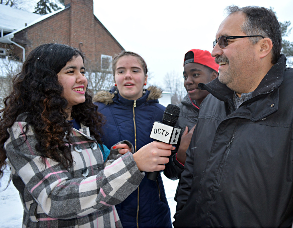 Crossroads resident Diyana (far left) interviews Detroit Pistons Coach Stan Van Gundy for Oxford Community Television. Watching in the background are fellow Crossroads residents Jessica (left) and Keylen. Photos by C.J. Carnacchio.