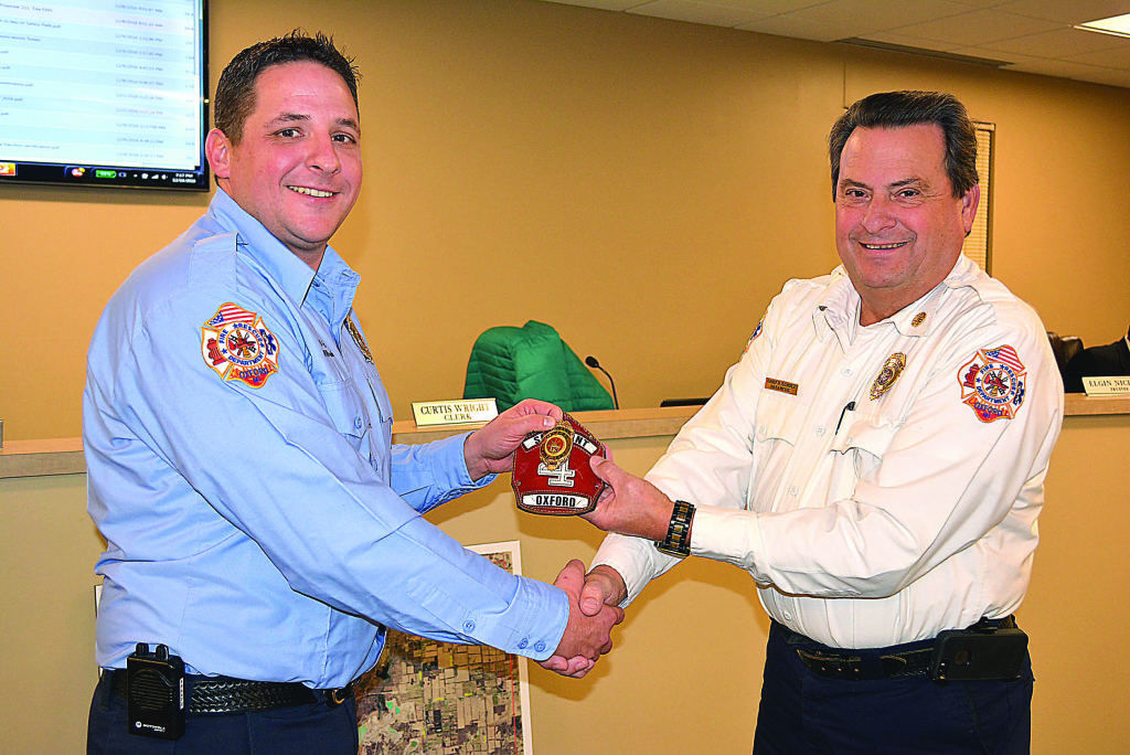 Oxford Fire Sgt. Benjamin Frantz (left) receives his new leather helmet shield from Fire Chief Pete Scholz. Photo by C.J. Carnacchio.