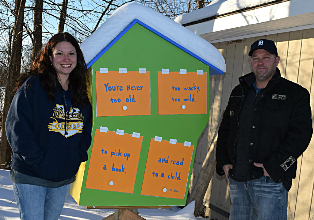 Michelle Candella (left) and Michael Audia pose next to the Little Free Library they erected in the Lake Villa Manufactured Home Community. Photo by Elise Shire.