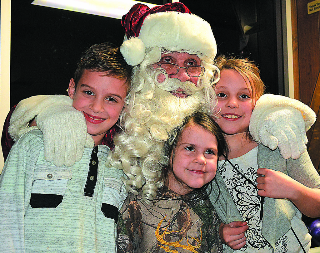 Posing for a photo with Santa Claus are (from left) Oxford residents Jay Ostrowski, Madalyn Ramaekers and Halie Ramaekers. Photo by C.J. Carnacchio.