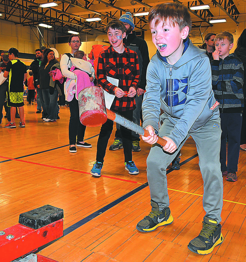 Testing his muscles by playing the traditional strongman game is OES fourth-grader Ethan Kussner.