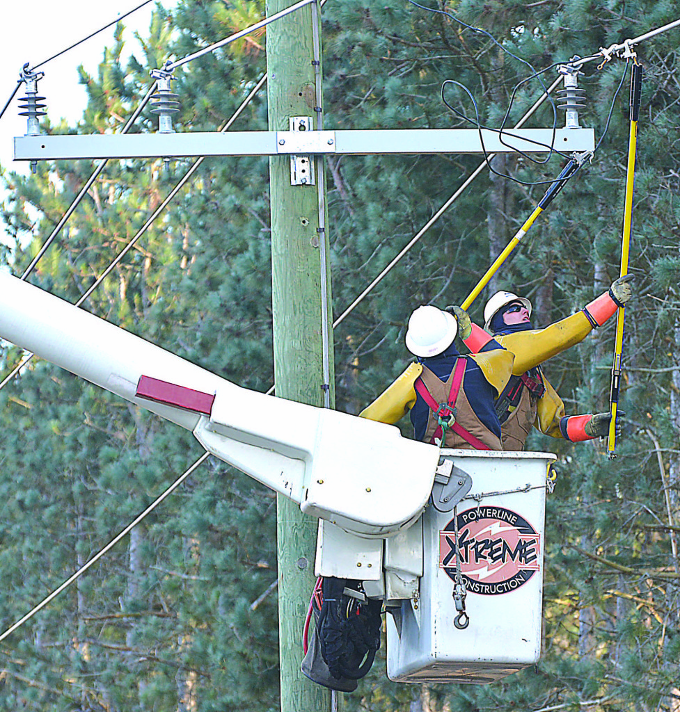 Workers finish installing a new power pole just east of Dunlap Rd. and just north of the Oxford Township Hall.