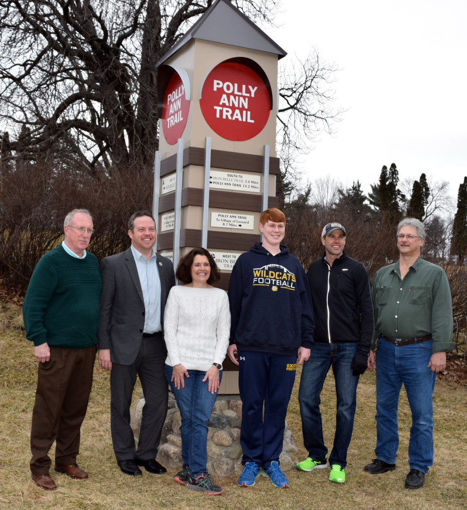 Oxford Twp. Supervisor Bill Dunn (from left), Orion Twp. Supervisor Chris Barnett, Polly Ann Trail Manager Linda Moran, OHS Sophomore Brandon Groedhl, OHS Teacher David Okasinski, and Leonard Village President Mike McDonald gather near the new trail sign on W. Burdick St. Photo by Elise Shire.