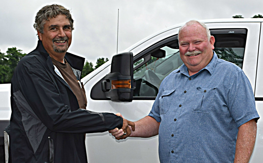 Kent Phillips (left), owner of Kent's Lawn Care, shakes hand with Addison Supervisor Bruce Pearson.