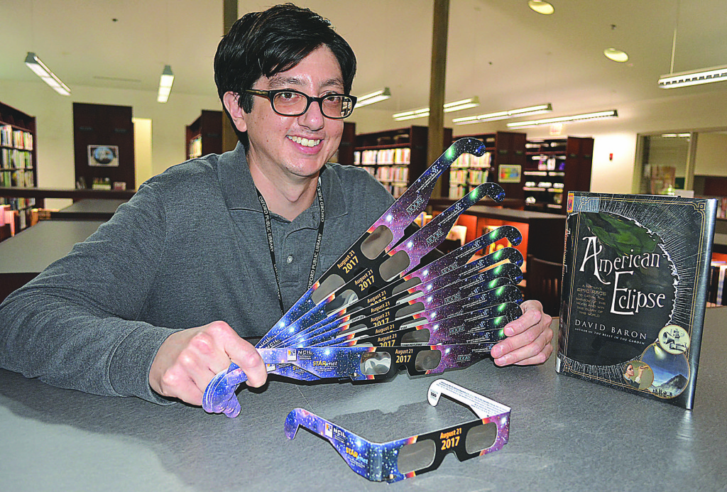 Ricardo Aguirre, a librarian assistant at the Oxford Public Library, holds a bunch of special eclipse-viewing glasses, which are available free to the public while supplies last. Photo by C.J. Carnacchio.