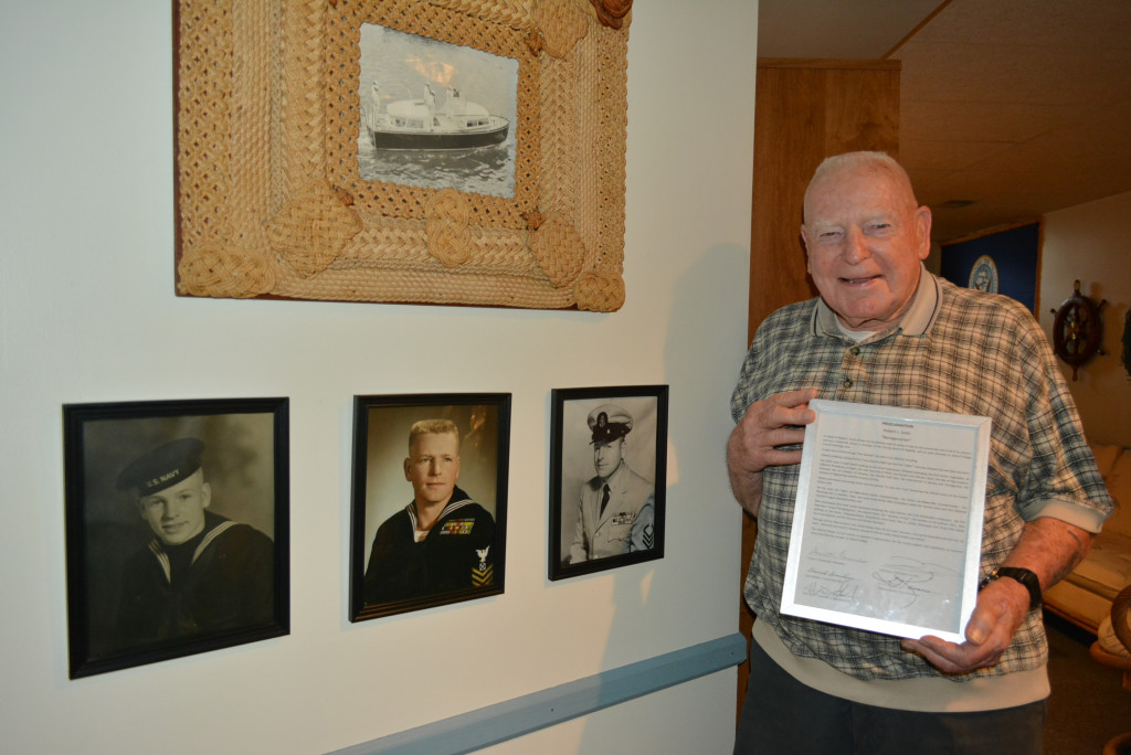 Longtime Oxford Village resident Robert L. Scott, Jr. was presented with a special proclamation in honor of his 90th birthday, which he will celebrate on Aug. 20. He's posing with photos of him from his days in the U.S. Navy. The photos on the wall show Scott (from left) when he was 17, 27 and 37 years old. Photo by C.J. Carnacchio.