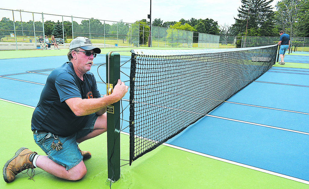 Park Supt. Jeff Kinasz puts the net up for one of Seymour Lake Park's four brand new tennis courts. Photo by C.J. Carnacchio.