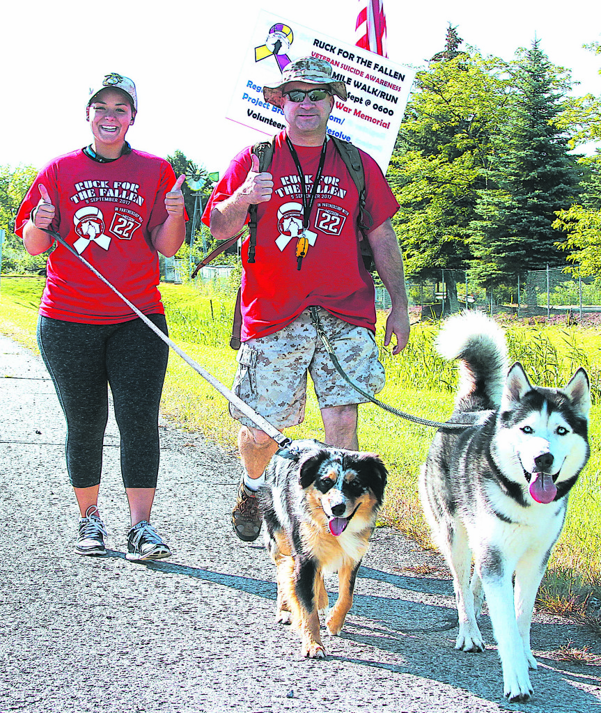 Lapeer residents Gary Morrell (right) and Kayla Morrell walk with their dogs Meeko (left) and Striker.