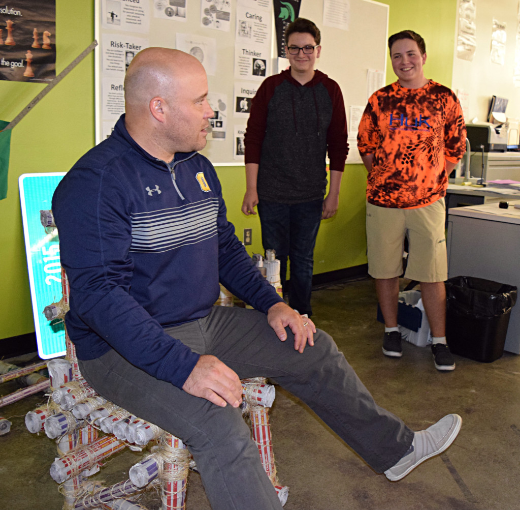 OHS students A.J. Laroche (left) and Austin Couch (right) built the chair that teacher Philip Kimmel is sitting in and judging. Photos by Elise Shire.