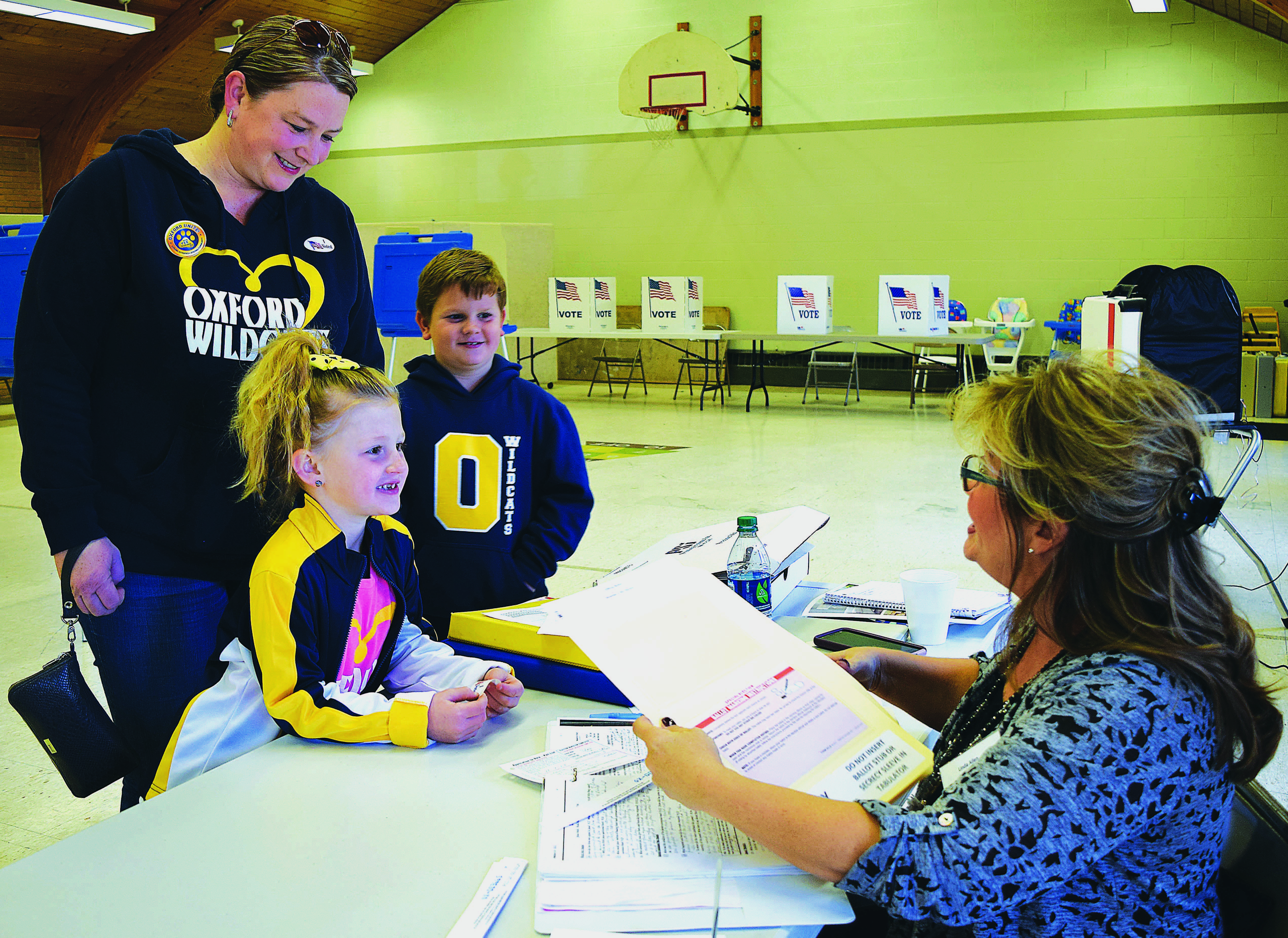 Voting as a family in Tuesday's school election are Oxford residents Danielle Wernis and her children, Chase, 7, and Gabrielle, 6. Assisting them at the Oxford Free Methodist Church is Precinct #3 Chairperson Linda Allen. Photo by C.J. Carnacchio.