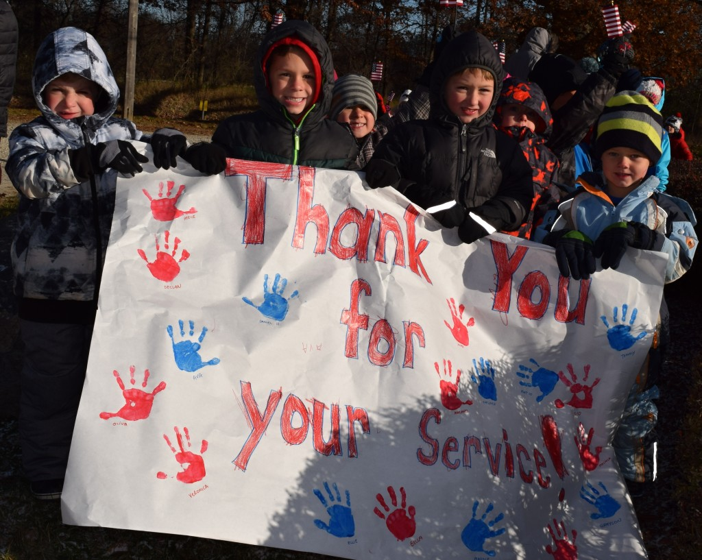 Holding a sign thanking veterans for their service are (from left) Kingsbury students Declan Saunders, Alec Dubey, Noah Griffith, and Tommy Rascher. Photo by Elise Shire.
