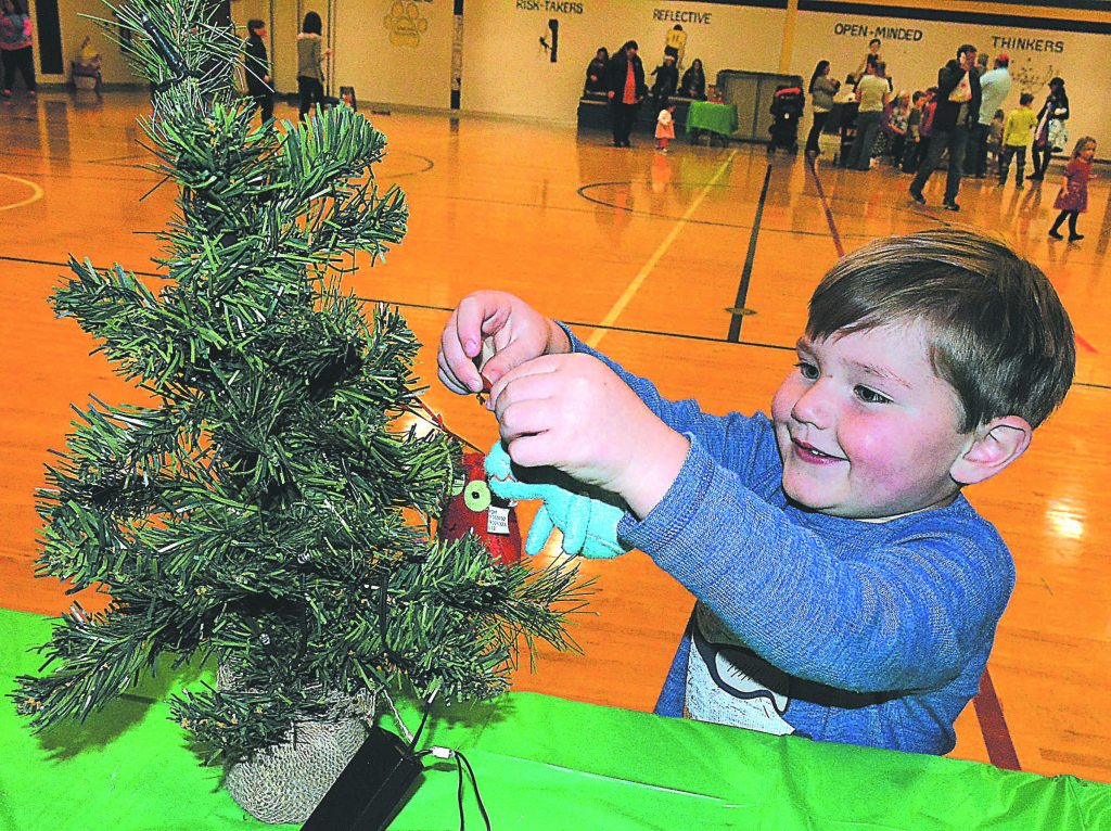 Luke Schutz, 3, of Oxford, participates in the Christmas tree decorating relay race. Photo by C.J. Carnacchio.