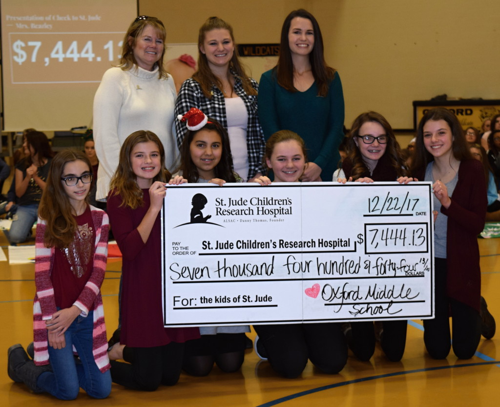 Volunteer Toni Casey (back row, from left) Intern Brianna Patrick and Senior Regional Representative Nicole Laidlaw accepted a check on behalf of St. Jude Children's Research Hospital from OMS students (from left) Allison Booth, Braydee Elling, Ella Flores, Aubrey Greenfield, Ella Klimowicz and Esme Roda. Photo by Elise Shire.