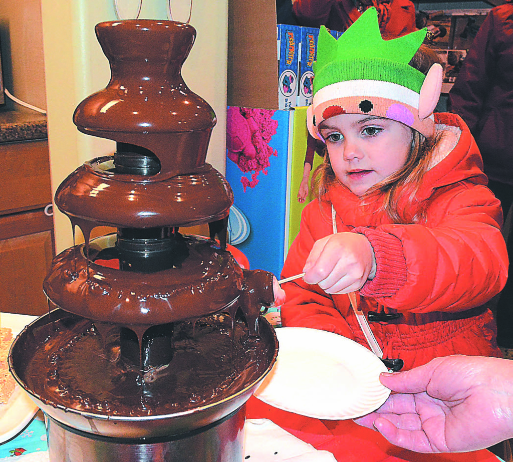 Betty Yagley, 4, of Oxford, drenches a marshmallow in chocolate. Photo by C.J. Carnacchio.