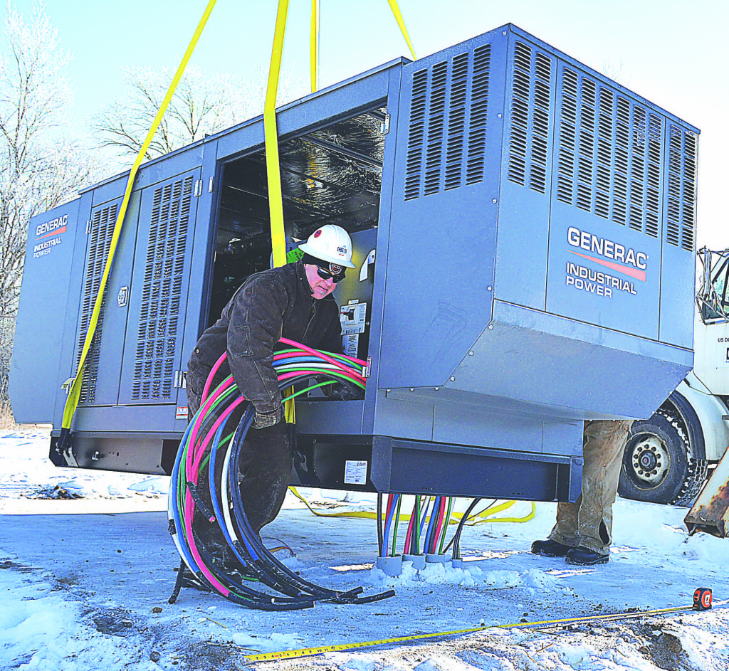 A worker helps install a 250-kilowatt industrial generator that will serve the Oxford Township Hall during power outages. Photo by C.J. Carnacchio.