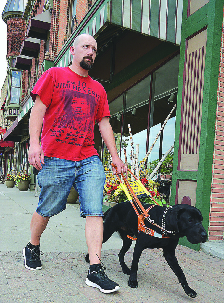 Oxford resident Justin Willcock is legally blind and has hearing loss in both ears. He walks around town with Alex, his guide dog.