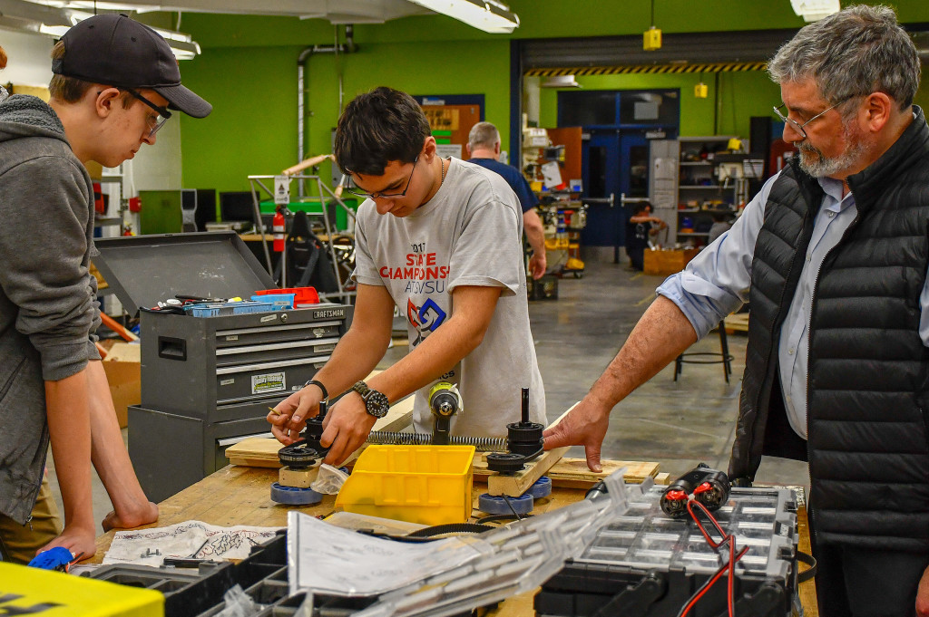 OHS students Alex Lundy and Brandon Hiscox, along with Mentor Andre LaRoche, help build the TORC 2137 robot. Photo provided.
