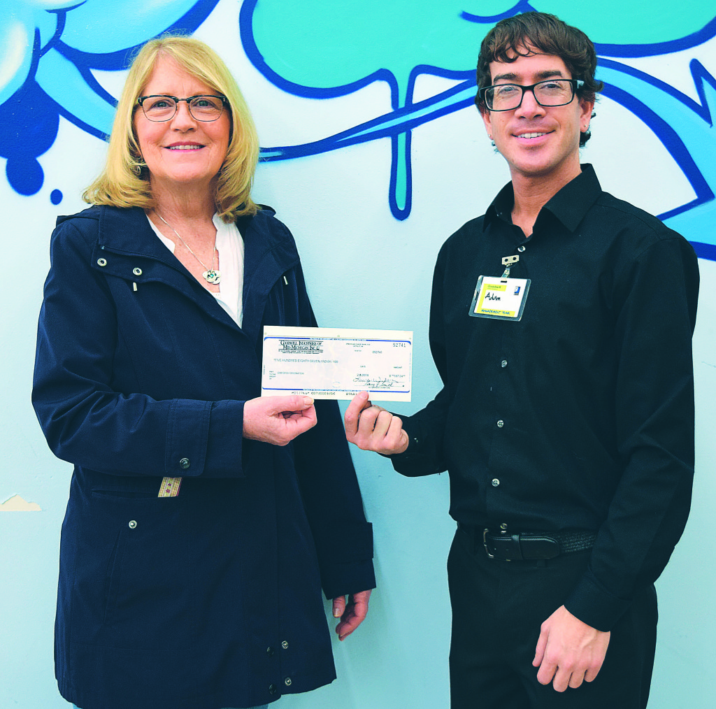 FISH Vice President Julie Howald (left) receives a $587 donation check from Adam Calimeri, assistant manager of the Goodwill store in Oxford. Photo by Elise Shire.