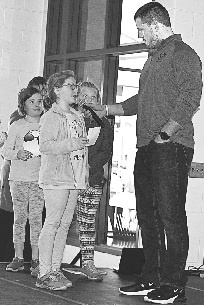 Cailyn Eller, an Oxford Elementary student, asks Line a question about reading. Photo by Elise Shire.