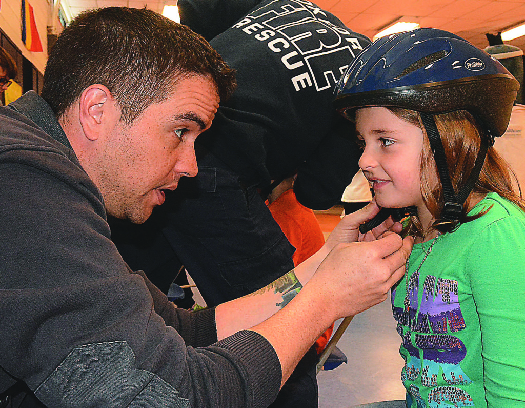 Clear Lake Elementary second-grader Tori Egbert gets fitted for a new bicycle helmet with the help of Oxford firefighter Justin Templeton. Photos by C.J. Carnacchio.
