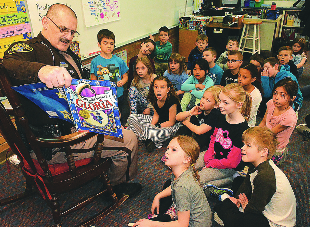 "Oakland County Sheriff's Reserve Deputy Bruce Mack reads ""Officer Buckle and Gloria"" to Clear Lake second-graders in teacher Jennifer Clemens' classroom. Photo by C.J. Carnacchio."