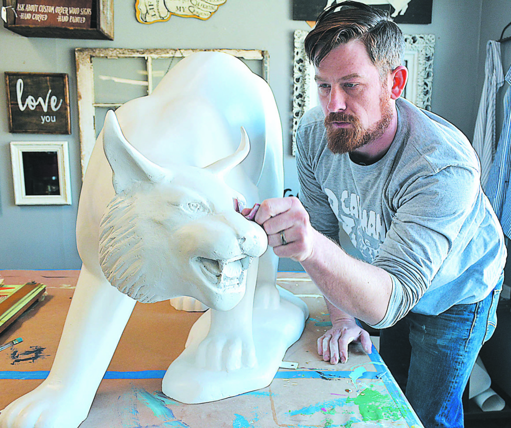 Craig Shagena, owner of Caveman & Pip in downtown Oxford, sands his Wildcat statue in preparation to paint it for Experience Oxford April 20-22. Photo by C.J. Carnacchio.