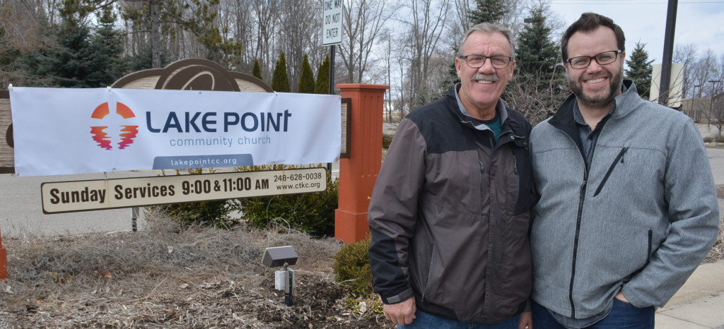 Senior Pastor Bob Holt (left) and his son, Executive Pastor Jesse Holt, stand beside the temporary sign for LakePoint Community Church. Photo by C.J. Carnacchio.