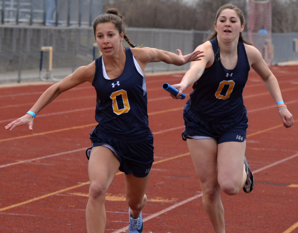 Emma Vanloon (left) reaches for the baton being handed off by Micah Dymond. Photo by C.J. Carnacchio.