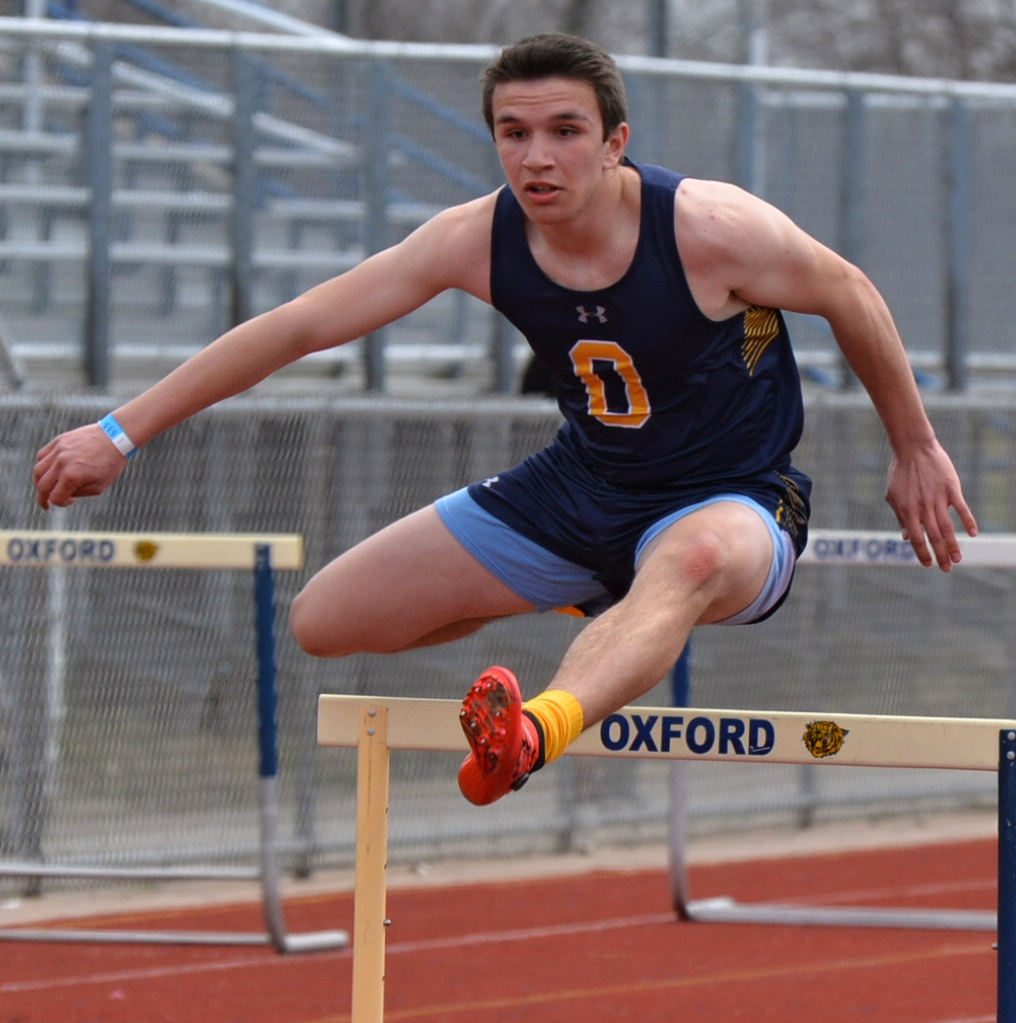 Oxford's Shane Ross leaps over a hurdle. Photo by C.J. Carnacchio.