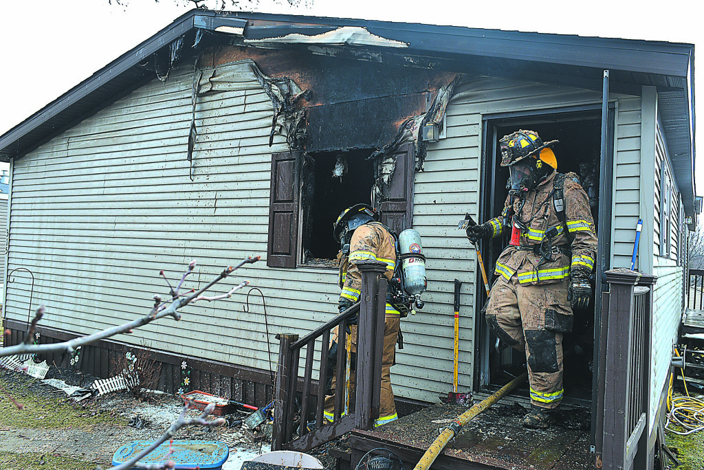 Oxford firefighters exit a manufactured home on Basket Branch in the Lake Villa community Friday afternoon following a fire that erupted in a bathroom. Photo by C.J. Carnacchio.