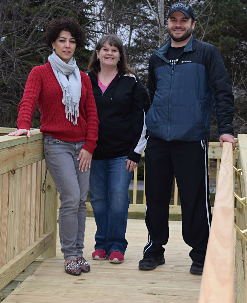 Marcie Gruenberg (center) stands on the deck of a wheelchair ramp built outside her family's Oxford home with the help of Guiding Star Foundation President Sophia Bong (left) and Vice President Joe Bongiovanni. Photo by Elise Shire.