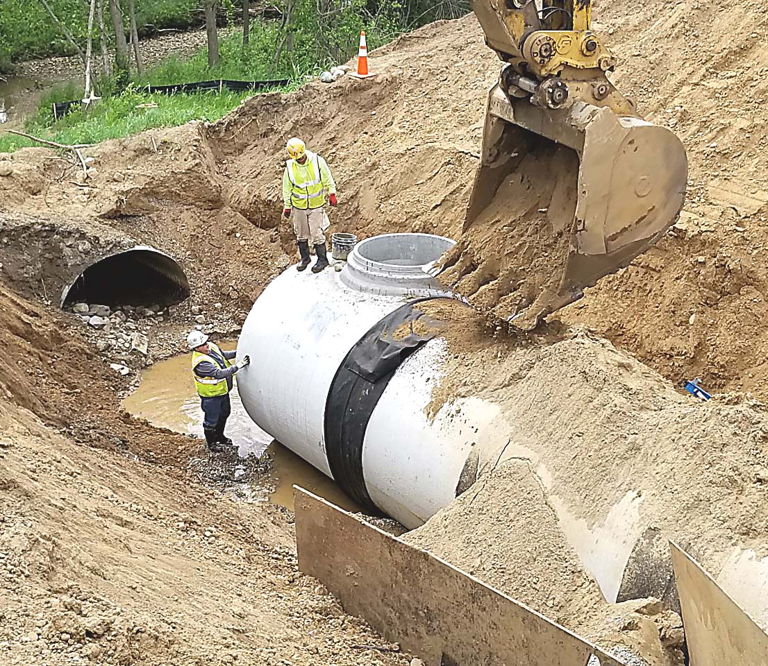 Workers install a reinforced concrete pipe with an 84-inch diameter as the new culvert that will carry the waters of Paint Creek beneath Wood Trail. Photo by Bill Dunn.