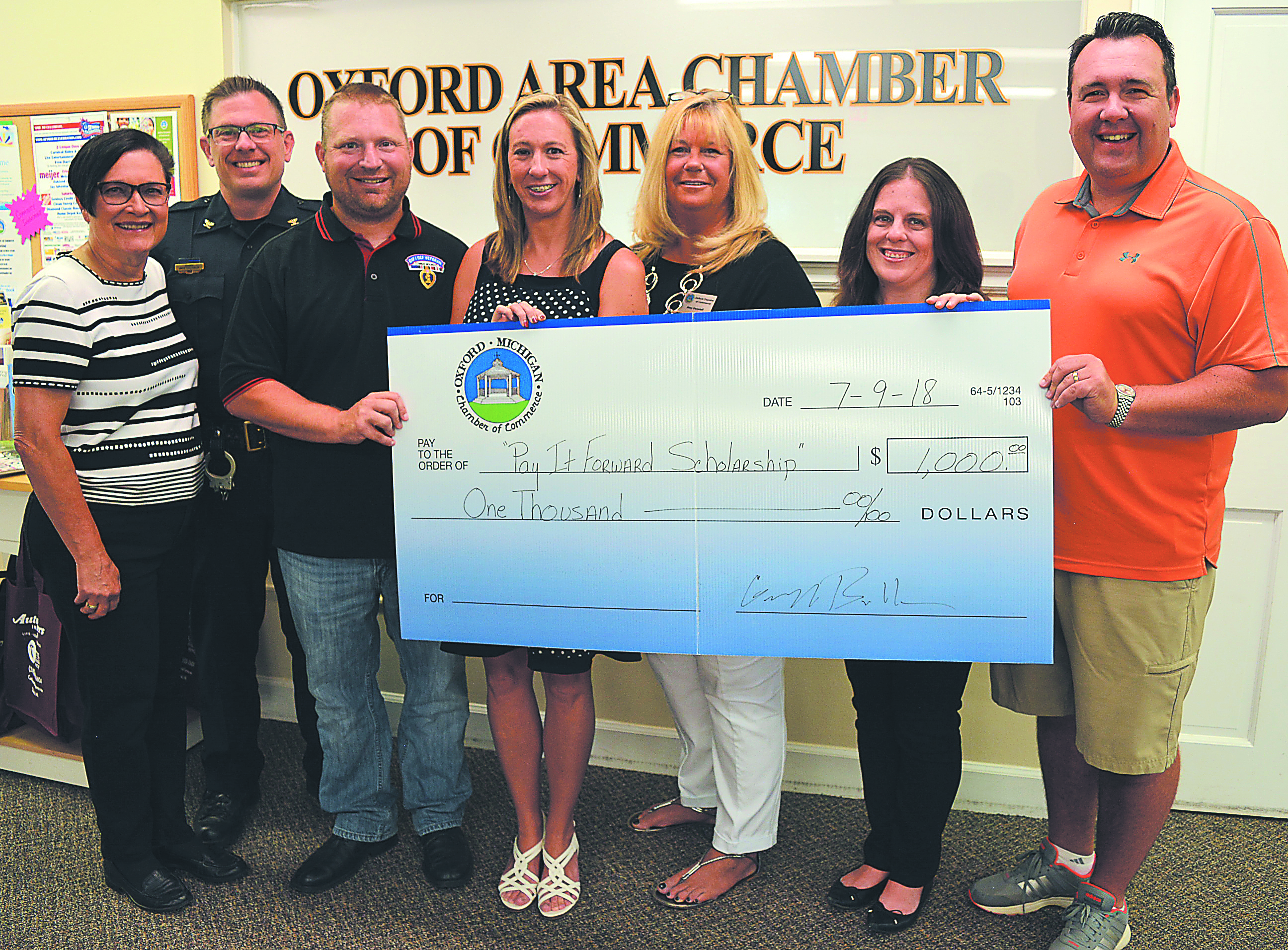 Holding the ceremonial $1,000 donation check for the Pay It Forward Scholarship are Oxford Chamber of Commerce President Deb Uren (from left), Oxford Village Police Chief Mike Solwold, Darrin and Amy Hafeli, Interim Chamber Director Amy Desotell and Chamber Board Members Alaina Sullivan and Geoff Bullen. Photo by C.J. Carnacchio.