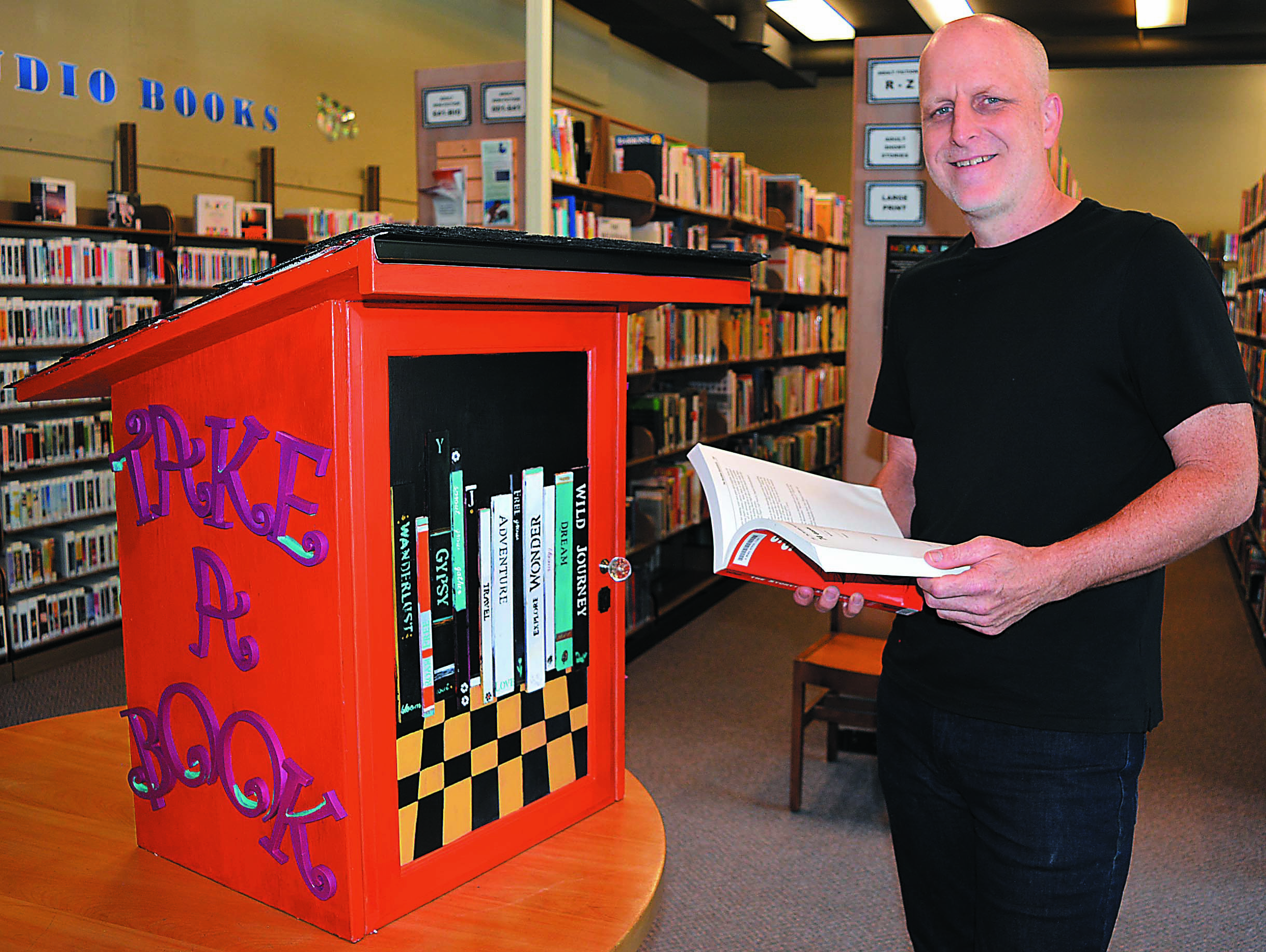 Addison Township resident Brian Howarth poses with the Little Free Library he built on behalf of the Addison Township Public Library. It will be placed along the Polly Ann Trail in Leonard. Howarth and his wife, Carolyn, will be honored as the Special People during Leonard's Strawberry Festival parade July 21. Photo by C.J. Carnacchio.