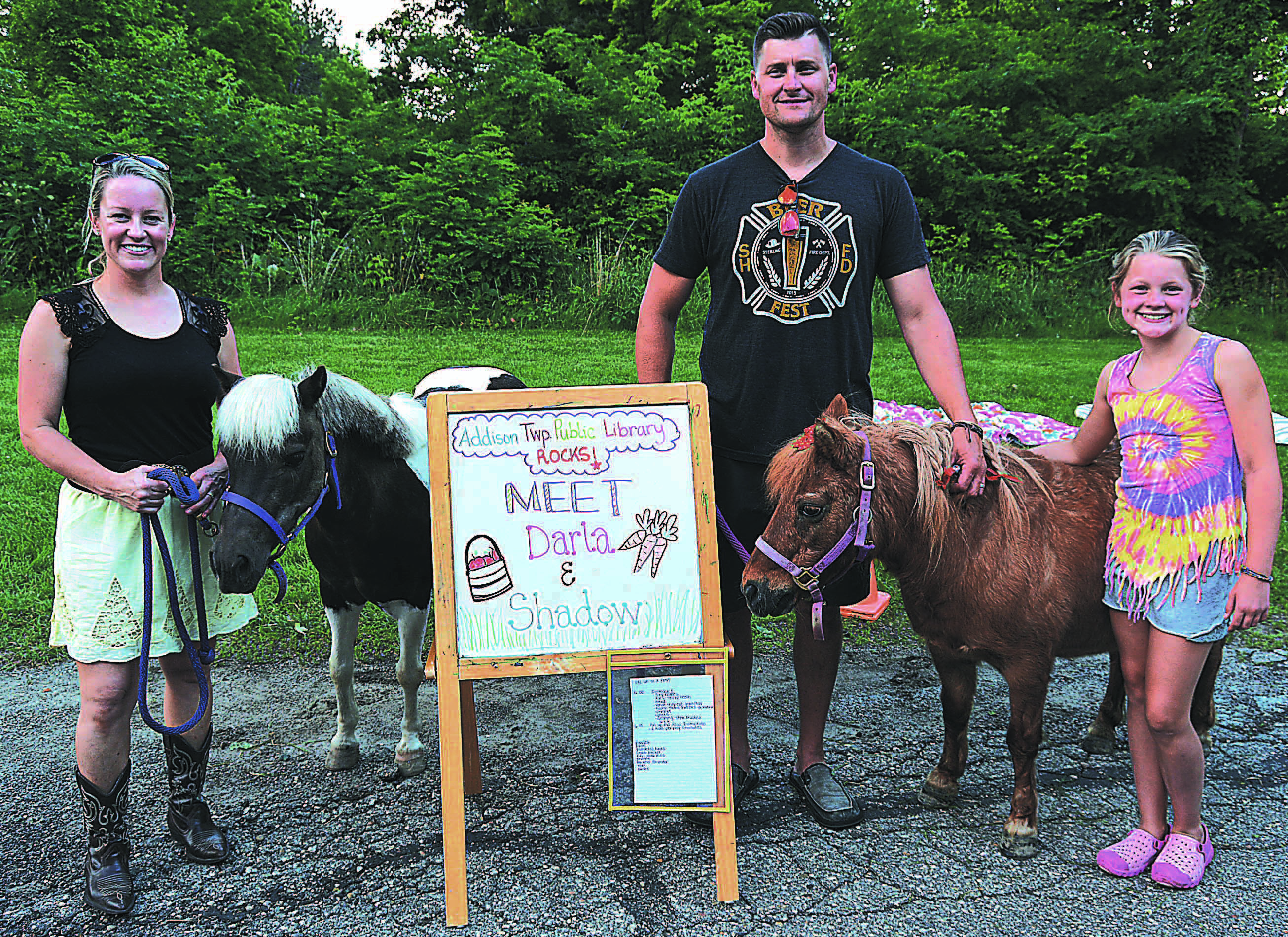 Addison residents (from left) Angie, Rich and Jane Feeney brought their miniature horses Shadow (left) and Darla to the Addison Township Public Library last week. Photos by C.J. Carnacchio.