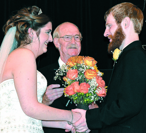 Retired Pastor Bob Service (center) officiated his 1,000th wedding ceremony Saturday at Oakwood Wedding Chapel in Oxford Township. He married Kaitlin Ormerod (left) and Lucas Conley. Photo by C.J. Carnacchio.