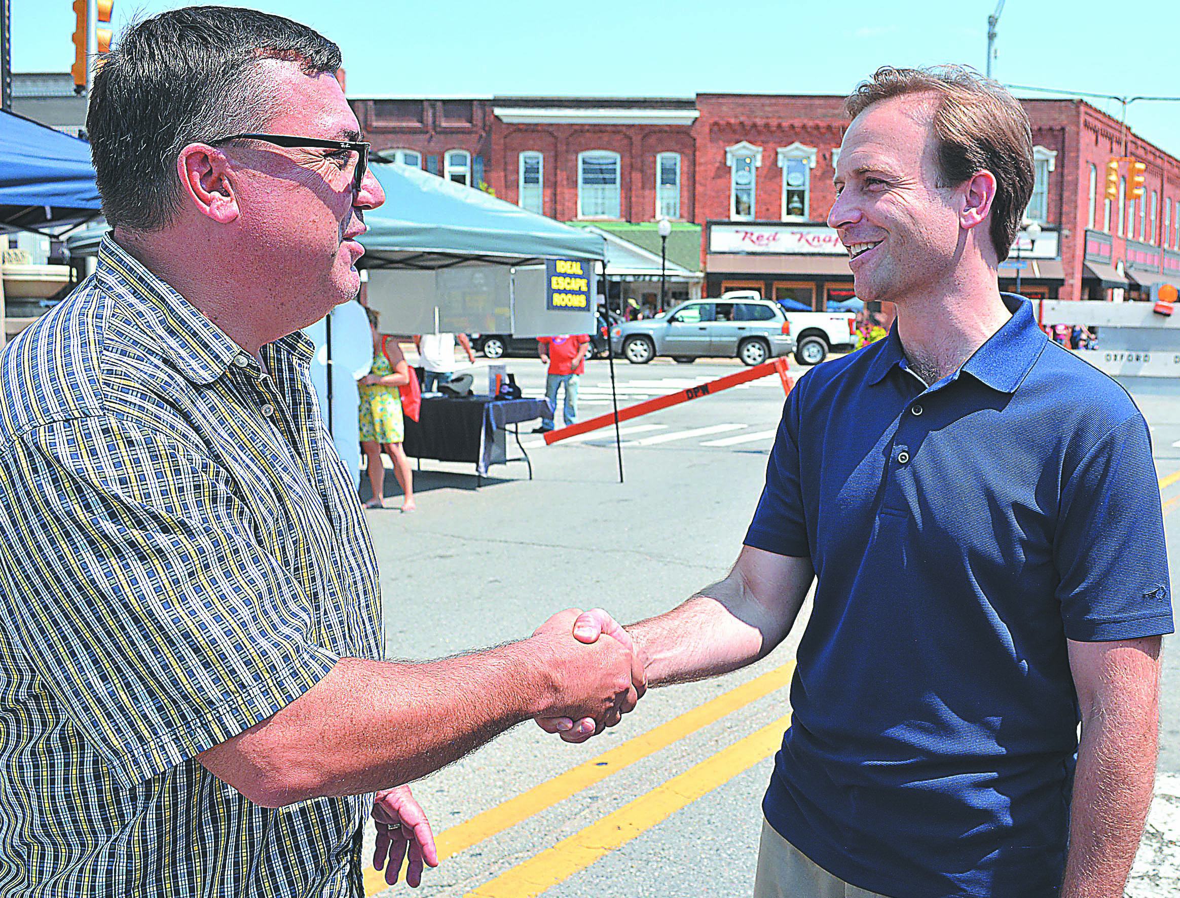 Lt. Gov. Brian Calley (right) shakes hands with Orion Twp. resident Tony Albensi Saturday during the Lone Ranger Festival in downtown Oxford. Albensi is a former Oxford Village councilman. Photo by C.J. Carnacchio.