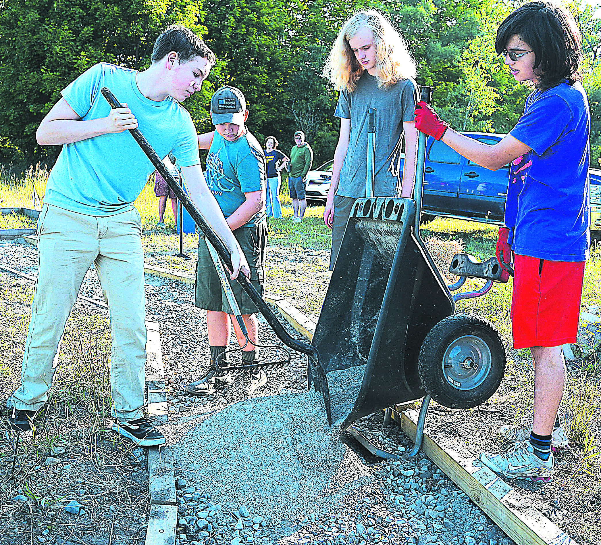 Members of Boy Scout Troop 366 spread material Saturday morning to create a small path that will link the Polly Ann Trail to a yet-to-be-built 12-foot-by-12-foot concrete pad with a picnic table. Pictured (from left) are scouts John Keller, Gavin Dell, Eagle candidate Logan Streeter and Ian Alexander. Photo by C.J. Carnacchio.
