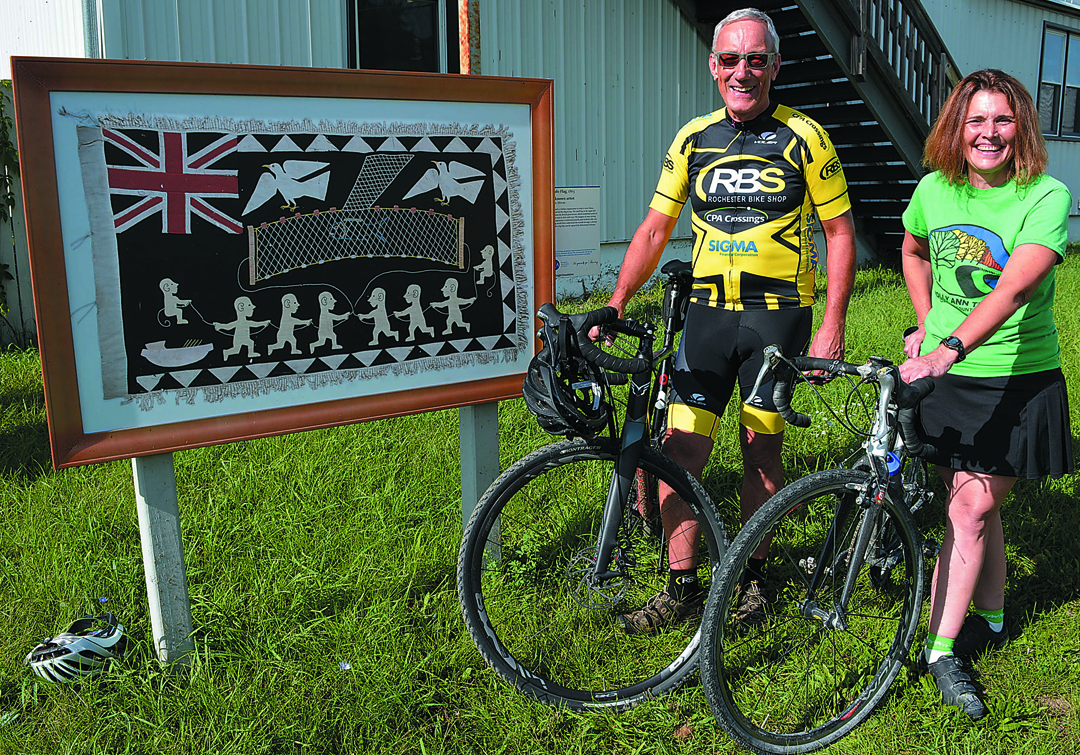 Polly Ann Trail Manager Linda Moran (right) and volunteer George Ingram, of Oakland Twp., are inviting folks to view replicas of art that hang in the DIA by going on a special free bicycle tour happening Sept. 16. Photo by C.J. Carnacchio.