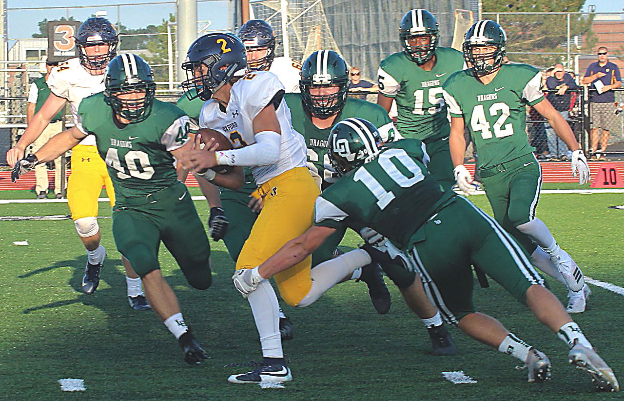 Surrounded by Dragon defenders, Oxford QB Drew Carpenter runs the ball. Photo by Joe St. Henry.