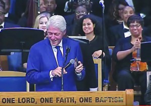 "Former U.S. President Bill Clinton uses his smartphone to play the 1968 hit song ""Think"" during Aretha Franklin's funeral at Detroit's Greater Grace Temple. Seated behind him to the immediate right is Oxford Schools orchestra director Natalie Frakes, who performed at the Aug. 31 funeral with the Aretha Franklin Orchestra. Image courtesy of WXYZ-TV Detroit."
