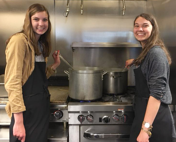 The Blair sisters cook food while volunteering at Grace Centers of Hope in Pontiac with the I'm 3rd student volunteer group. Photo provided.