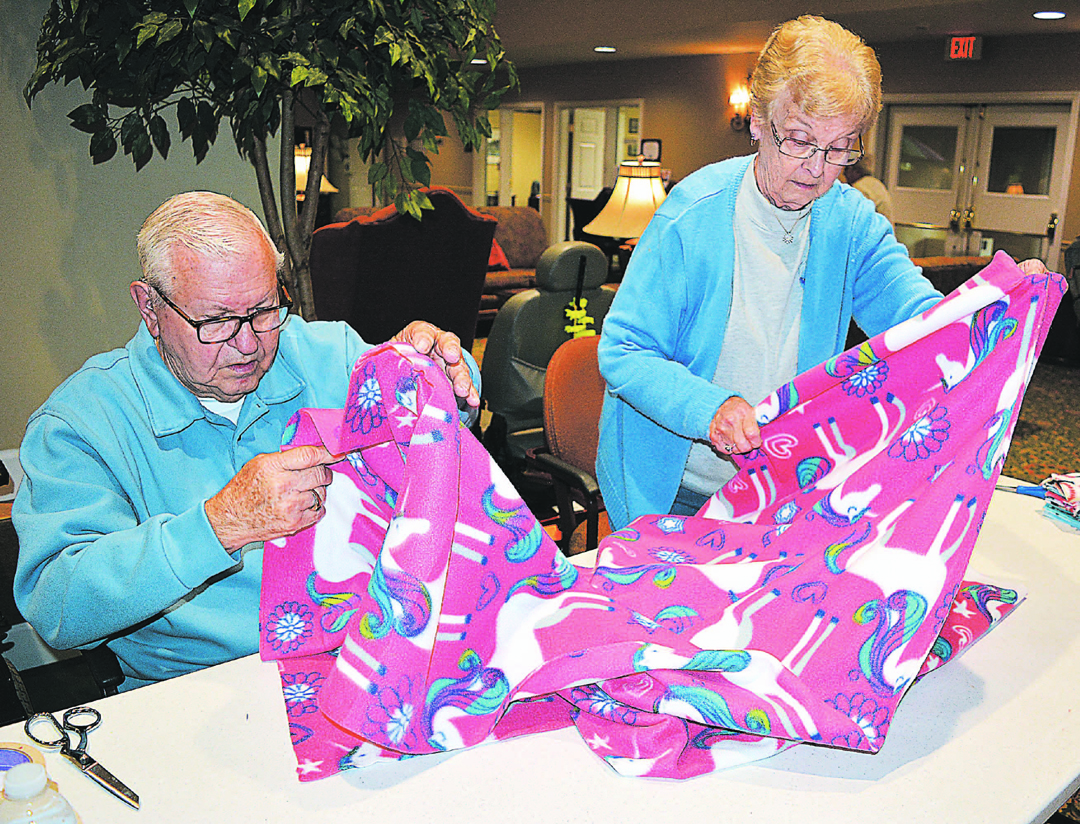 Independence Village residents Jerry and Jackie Bambousek work together on a unicorn-themed blanket for Project Linus. Photo by C.J. Carnacchio.