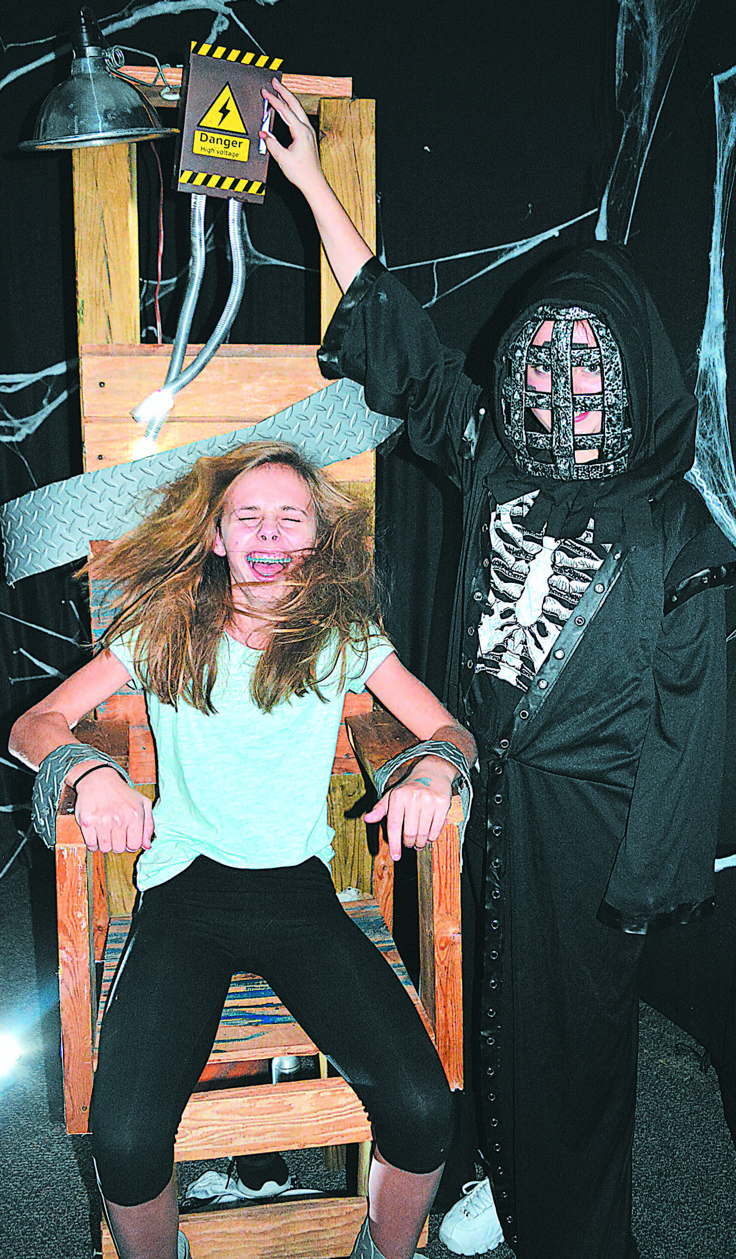Taking a ride in Old Sparky is OMS eighth-grader Rachael Albrecht. Executing her is Nevaeh Britt, an OMS seventh-grader. Photo by C.J. Carnacchio.