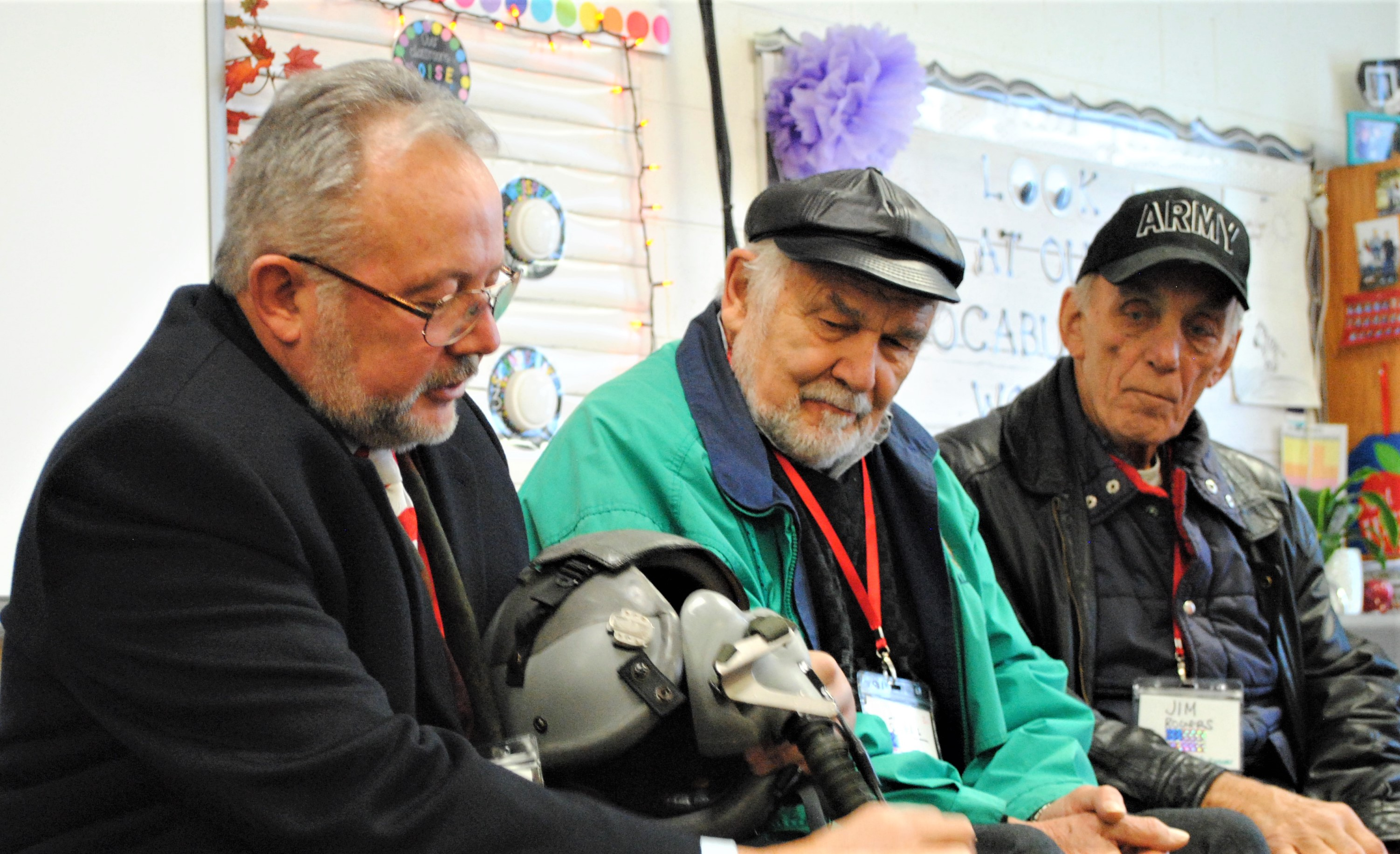 While some came with memories, others came with mementoes from their time in the service for students to see. Greg Gonyea had his air helmet and parachute pack in tow for a class of second-graders to put their hand on. With him is veterans Lloyd Schmaltz and Jim Rogers. Photo by Shelby Tankersley.