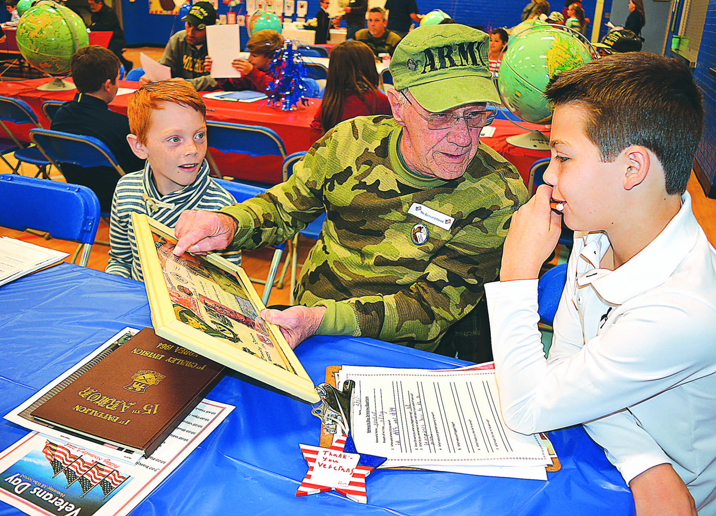 Gunnar Johnson (center), a U.S. Army veteran who served from 1963-64, shares his military experiences with fifth-graders Gavin Lewis (left) and Finn McDevitt. Photo by C.J. Carnacchio.