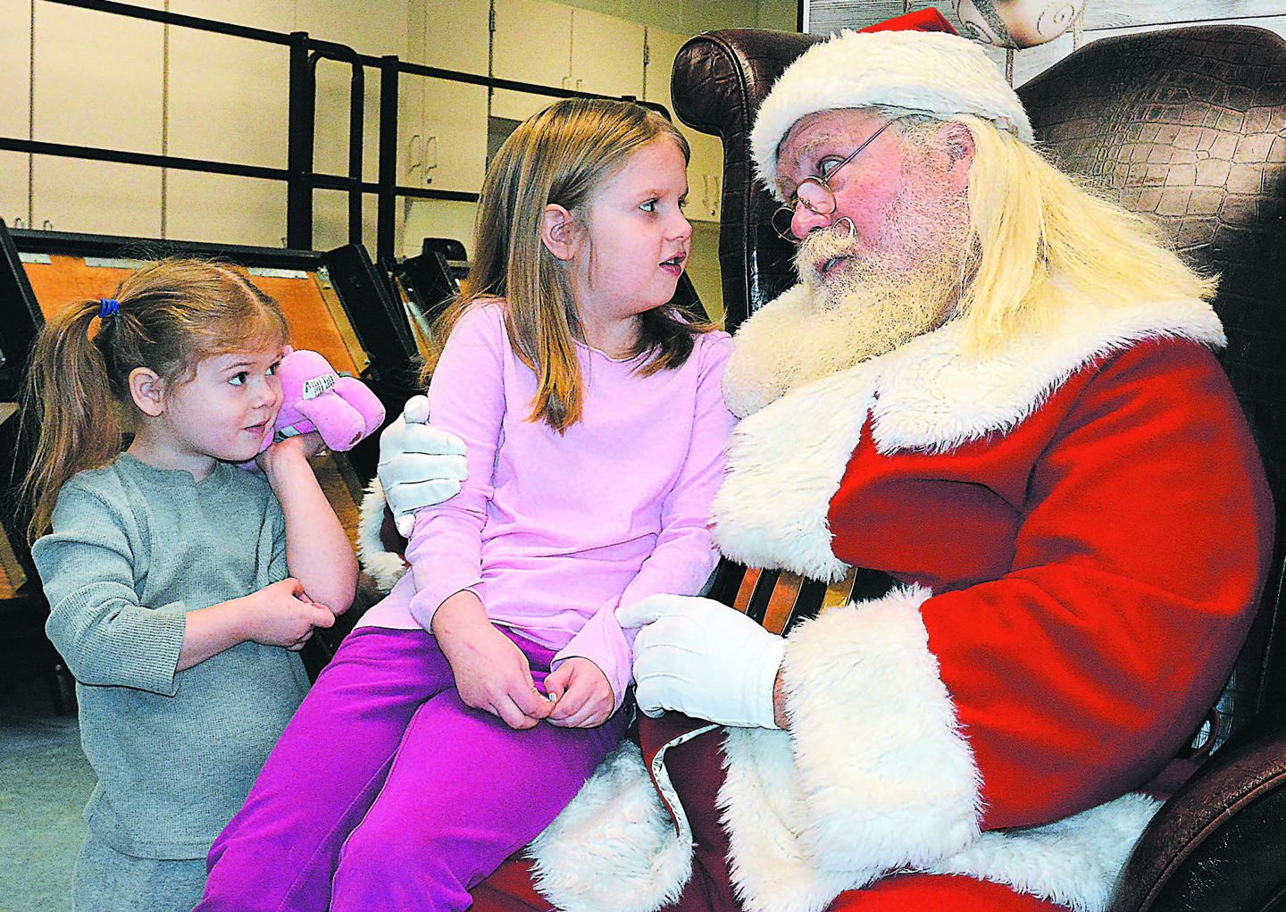 Visiting with the one and only Santa Claus are sisters Lena Starzyk (left), 3, and Sophia, 6. Sophia is a first-grader at Lakeville Elementary School. Photo by C.J. Carnacchio.