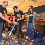 (From left) OMS robotics mentor Dennis Hurst and student Gavin Shafer make some adjustments with assistance from OHS robotics students Keira Houston and Jason Grabowski. Photo by C.J. Carnacchio.