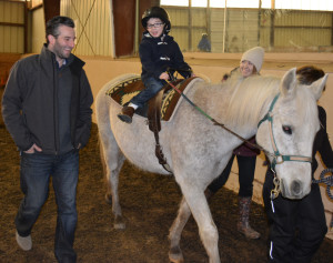 Five-year-old Jackson Picklo, this year's Star Student Rider at the Banbury Cross Therapeutic Riding Center in Metamora Township, rides Sassy, a 23-year-old Arabian horse, while talking to his dad Ryan. Photo by C.J. Carnacchio.